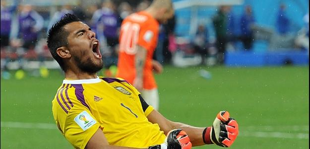 Romero comemora pênalti defendido. Ao fundo, Sneijder lamenta erro